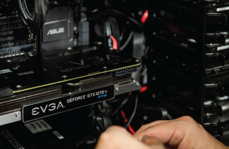 Technician plugins in EVGA GeForce GTX1070Ti video card into ASUS motherboard on PC