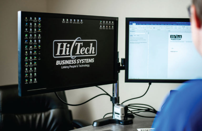 Hi-Tech employee edits a document on a dual-screen computer in his office in Grande Prairie