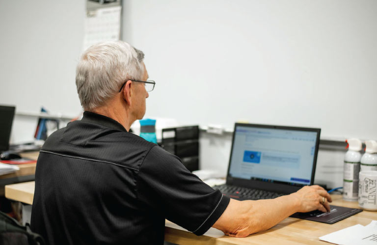 Computer repair technician inspects a laptop at the Hi-Tech service center in Grande Prairie
