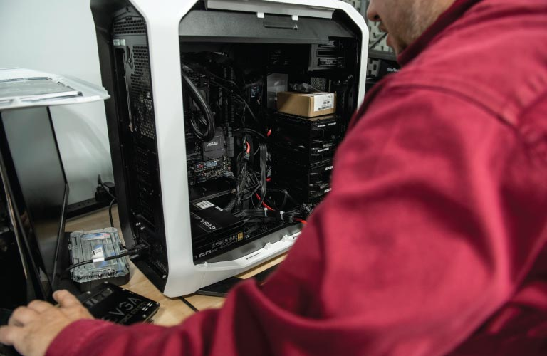 A Hi-Tech computer repair specialist prepares to replace broken graphics card in open PC tower case