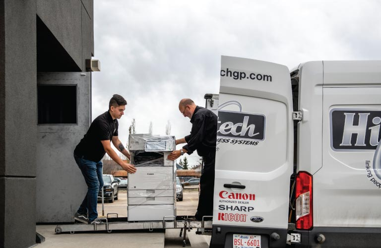 Two employees load a multi-functional printer (MFP) into a company delivery van