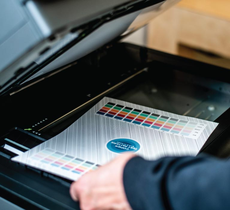 An employee tests a photocopier with a color and pattern test sheet to ensure its working properly