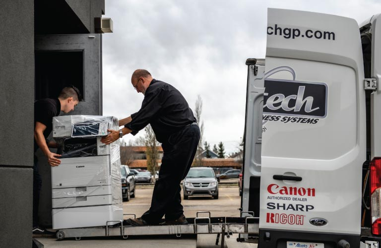 Two staff members load Canon photocopier for office equipment rental onto delivery van
